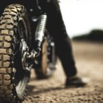 Rear view of man sitting on cafe racer motorcycle on a dusty dirt road, close up of tire.